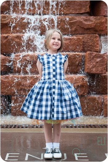Girl modeling retro dress in front of water feature