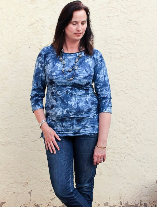 Woman standing and wearing blue top made from The Maritiem Top Sewing pattern