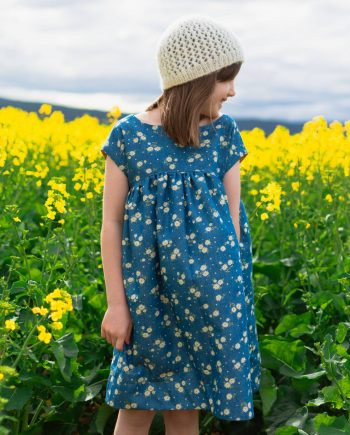 A girl looking off into the distance wearing a dress made from The Nieuw Dress sewing pattern in flowers