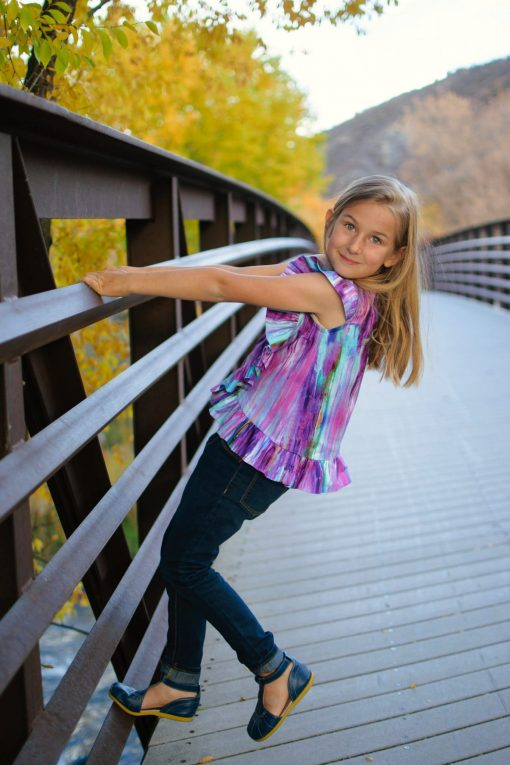 girl leaning off of railing wearing purple ruffle blouse and jeans