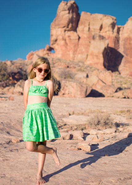 girl wearing green retro play suit made from the schatje skirt sewing pattern with Michael Miller Fabric in front of pink rocks and cacti in the desert