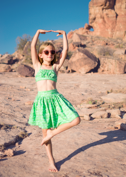 girl wearing green retro play suit made from the schatje skirt sewing pattern in front of pink rocks and cacti in the desert