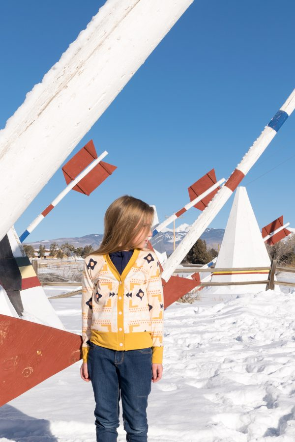 Girl wearing southwest style cardigan made from the Academie Cardigan sewing pattern in the snow in front of giant arrows.