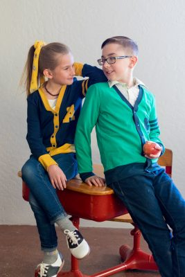 Boy wearing green and blue cardigan and girl wearing blue and yellow cardigan made from the academie cardigan sewing pattern