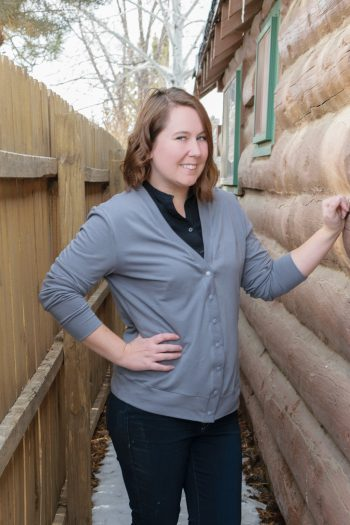 Woman wearing gray cardigan made from the adult academie Cardigan sewing pattern, standing by log cabin.