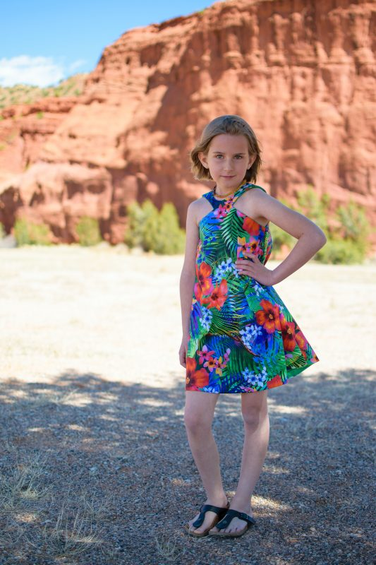 Girl wearing sleeveless tropical print dress using The Driehoek Dress sewing pattern and Tropical Dreams fabric from Michael Miller.