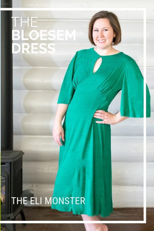 The Bloesem Dress Sewing pattern in solid green in front of log wall.