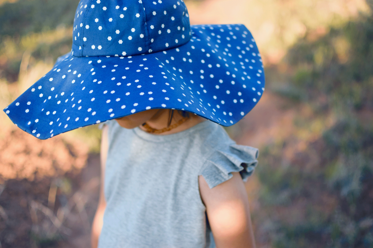 Girl in desert wearing a blue oversized sun hat, an upcycled gray tank and floral scallop hem shorts.