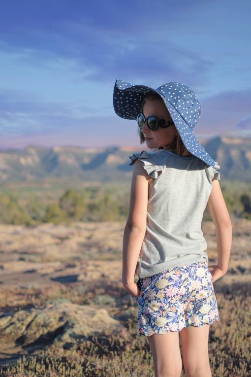 Girl in desert wearing an oversized hat using a hat sewing pattern, upcycling tank, and scalloped hem shorts.