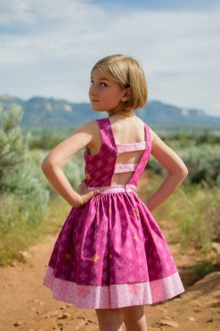 Girl wearing purple dress made from the pindakaas sundress sewing pattern in sage desert.