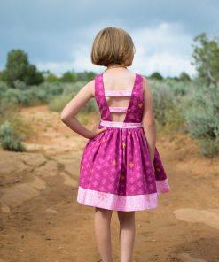 Back of girl wearing purple dress made from the pindakaas sundress sewing pattern in sage desert.