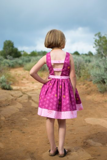 Back of girl wearing purple dress made from the pindakaas sundress sewing pattern in sage desert.
