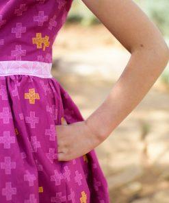 Closeup of girl wearing purple dress made from the pindakaas sundress sewing pattern in sage desert.