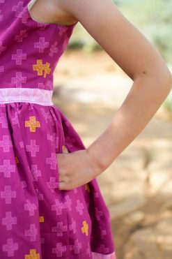 Closeup of girl wearing purple dress made from the pindakaas sundress sewing pattern in sage desert.