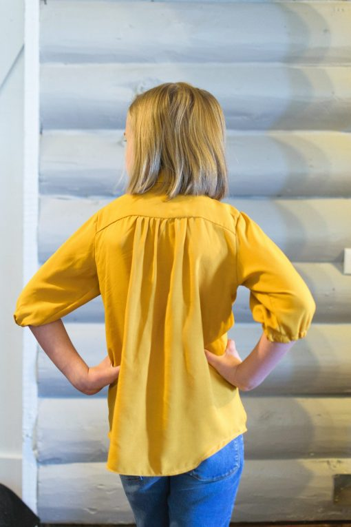 A girl facing away from the camera wearing a yellow blouse made from the muisje blouse sewing pattern