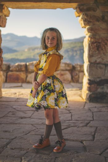 girl in yellow blouse and plum pinafore standing in doorway.