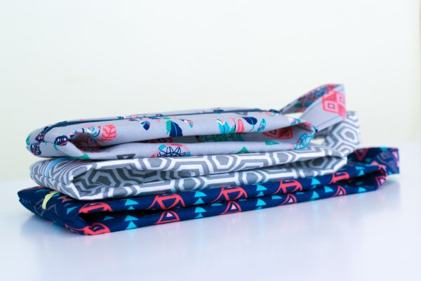 A stack of toer bags made from the sewing pattern flattened and stacked on a white surface