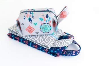 A stack of toiletry bags made from the toer sewing pattern stacked on a white table
