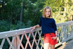 girl wearing red sailor shorts and blue top on a bridge.