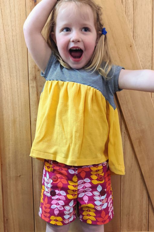 girl wearing floral shorts made from the oceaan shorts sewing pattern.