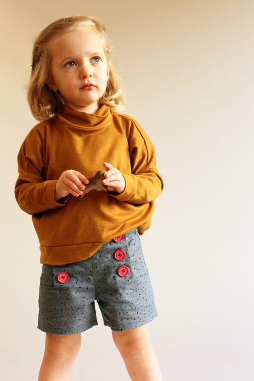 girl wearing grey shorts made from the oceaan shorts sewing pattern