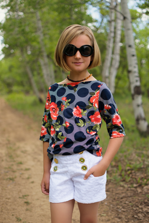 Girl in woods wearing white eyelet sailor shorts made from the oceaan shorts sewing pattern.