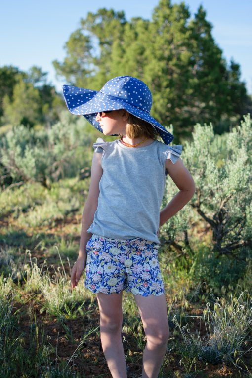Girl wearing blue polka dot sunhat made from the Wolkje Hat sewing pattern.