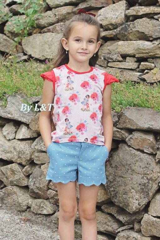 Girl standing in front of rock wall wearing blue shorts made from the blij shorts sewing pattern