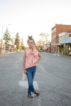 girl wearing pink portret top made from a blouse sewing pattern and standing in the street of a small town