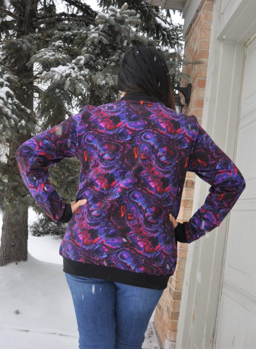 The back of a woman wearing a purple swirl bomber jacket made from the hagelslag jacket sewing pattern