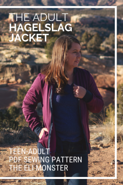 Woman wearing a maroon bomber jacket in front of a desert landscape looking off to the side with her hand on the zipper made from the Hagelslag Jacket sewing pattern.