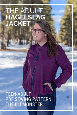 Woman standing in pine trees in the snow wearing plum track jacket made from The Hagelslag Jacket sewing pattern